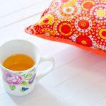 Beautiful orange cushion with floral print on a white wooden background, decoration of interior. A cup of hot tea in the morning. Zone for a comfortable reading and breakfast.