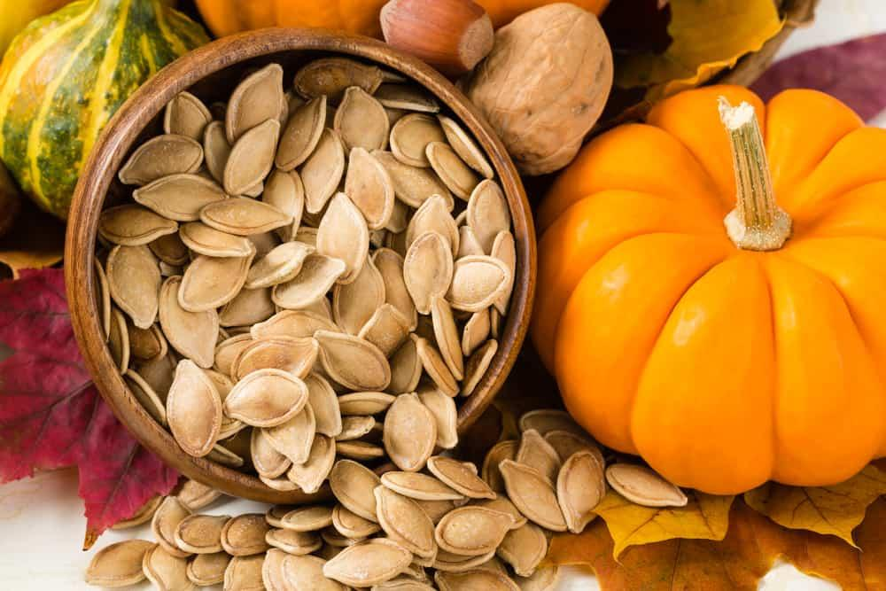 Healthy pumpkin seeds spill from a round wooden bowl surrounded by autumn leaves, nuts, gourds and a tiny pumpkin